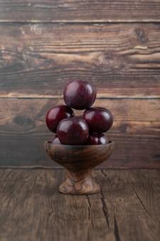 Una ciotola di legno con prugne viola sane fresche sul tavolo di legno.