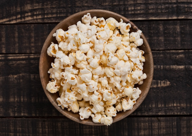 Wooden bowl with fresh salted popcorn on wooden background