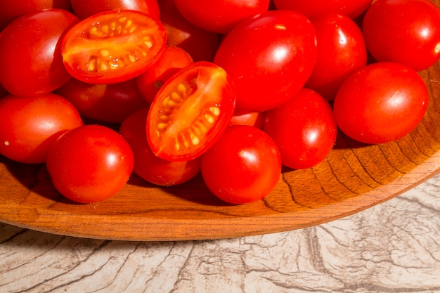 Wooden bowl with grape tomato on wooden background