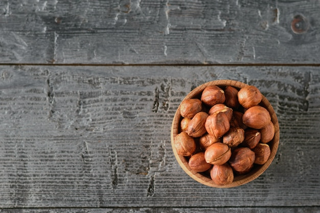 Wooden bowl with hazelnuts on black wooden table. the view from the top.
