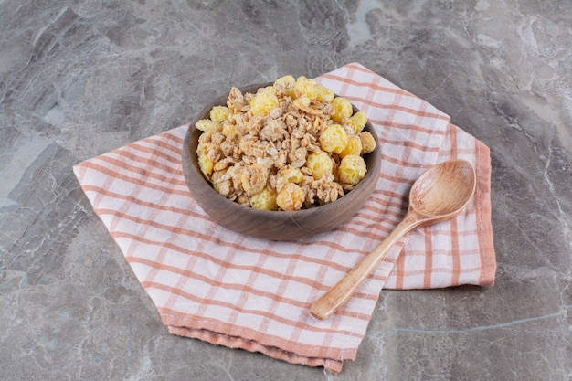 Una ciotola di legno con fiocchi di mais sani e un cucchiaio di legno vuoto.
