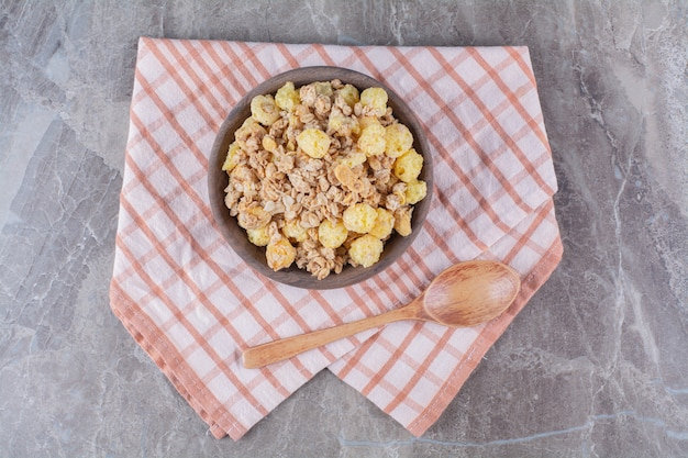 A wooden bowl with healthy cornflakes and an empty wooden spoon .