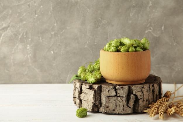 Деревянная миска с хмелем и пшеницей на белом деревянном фоне, место для текста