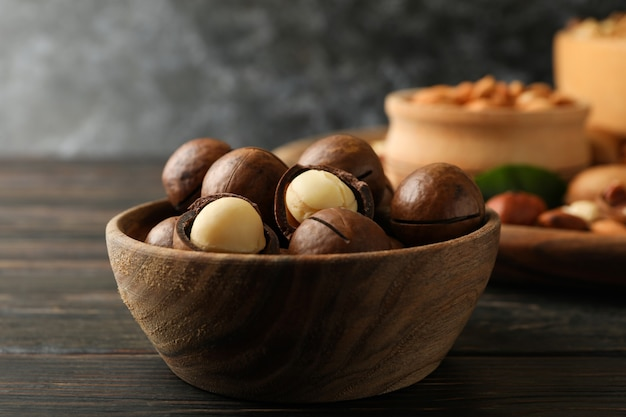 Wooden bowl with macadamia nuts on wood wall, close up