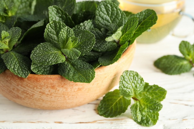 Wooden bowl with mint and tea on wooden table, close up