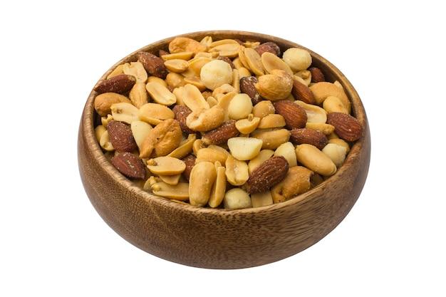 白い背景のミックスナッツと木製のボウル。健康食品とスナック。ナッツ、ピスタチオ、アーモンド、ヘーゼルナッツ、カシューナッツ