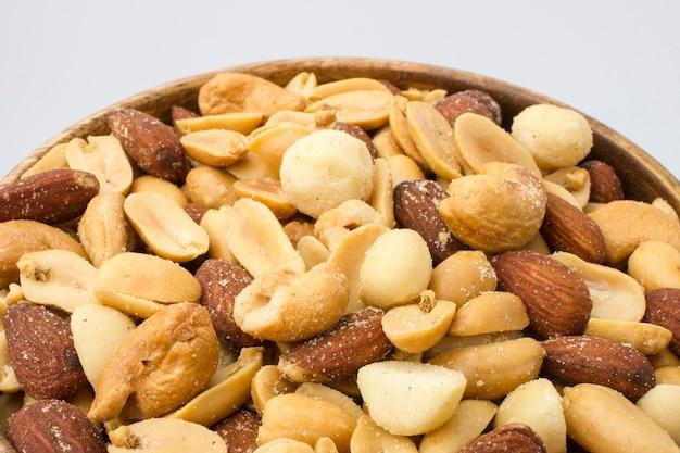 白い背景のミックスナッツと木製のボウル。健康食品とスナック
