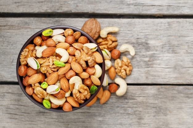 Деревянный шар с смешанными гайками на деревянном сером цвете. грецкий орех, фисташки, миндаль, фундук и кешью, грецкий орех.