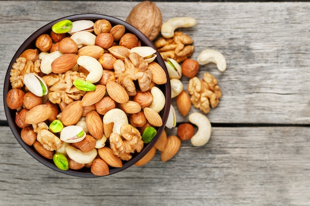 Wooden bowl with mixed nuts on a wooden gray surface