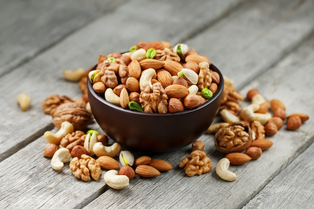 Wooden bowl with mixed nuts on a wooden gray . walnut, pistachios, almonds, hazelnuts and cashews, walnut.