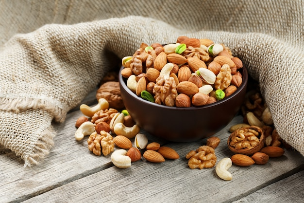 Wooden bowl with nuts on a wooden background, near a bag from burlap.
