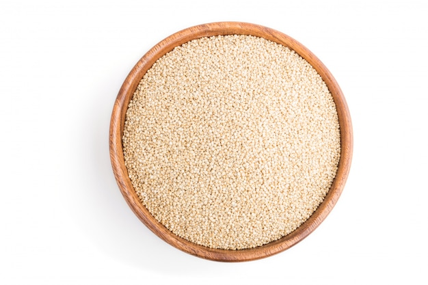 Wooden bowl with raw white quinoa seeds isolated on white background. top view.