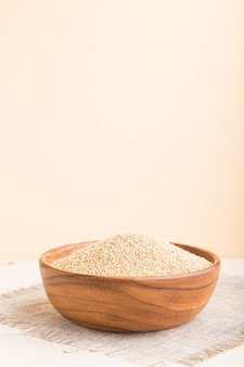 Wooden bowl with raw white quinoa seeds on a white and orange wooden background. side view, selective focus.