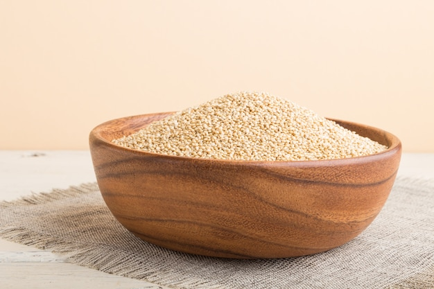 Wooden bowl with raw white quinoa seeds on a white wooden background. side view, close up.