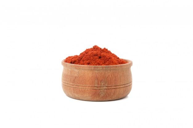 白で隔離される赤唐辛子粉末の木製ボウル