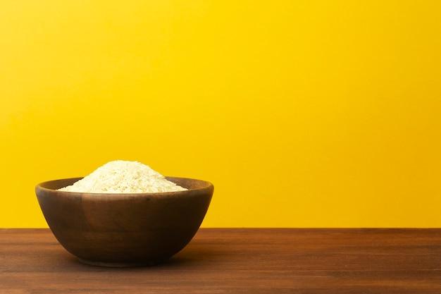 黄色の背景にご飯と木製のボウル。テーブルの上にアジアのインドの米バスマティと木の板