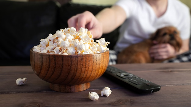 Wooden bowl with salted popcorn and tv remote.