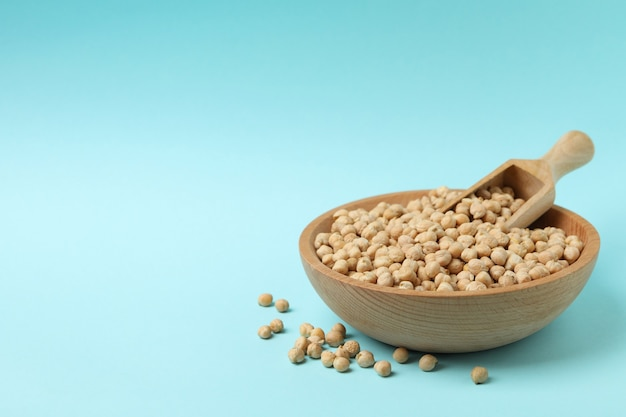 Wooden bowl with scoop and chickpea on blue