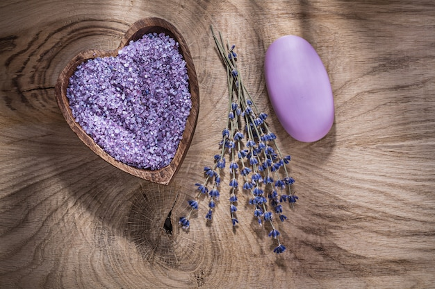 Wooden bowl with sea salt dry lavender bar of soap on wood board spa treatment concept