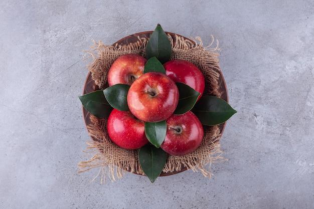 Деревянная миска с блестящими красными яблоками на каменной поверхности.