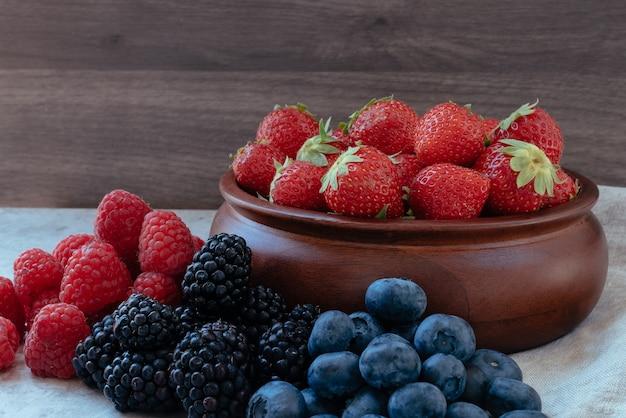 イチゴとその隣にブラックベリー、ブルーベリー、ラズベリーと木製のボウル