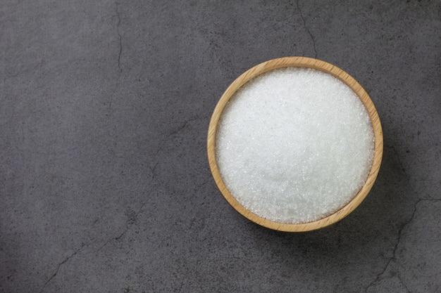 Деревянная миска с сахаром на черном бетоне