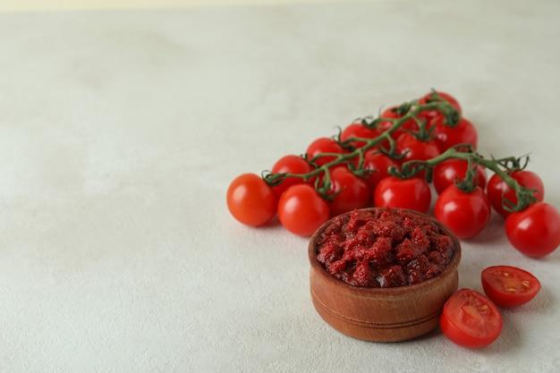白いテクスチャテーブルにトマトペーストとトマトの木製ボウル