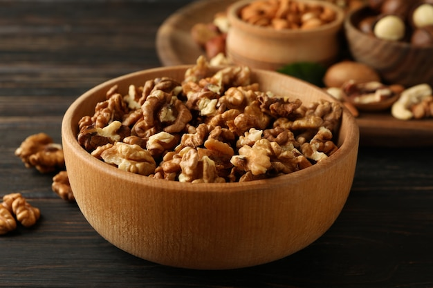 Wooden bowl with walnuts on wood, close up