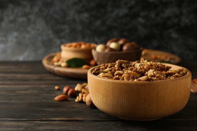 Wooden bowl with walnuts on wood