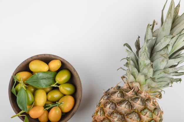 Wooden bowl of yellow kumquats and pineapple on white table.
