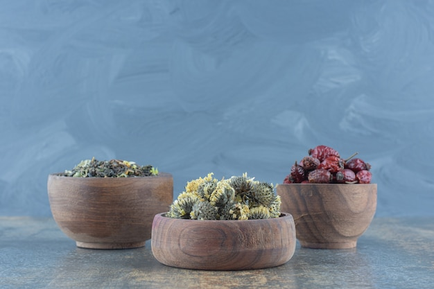 Wooden bowls of dried flowers and rosehips.