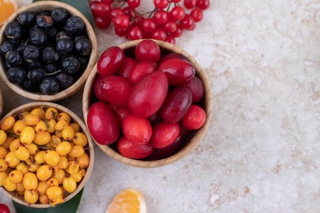 Ciotole di legno piene di deliziosi frutti di bosco