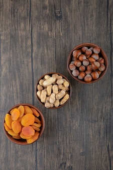 Wooden bowls full of healthy nuts with dried apricot fruits on wooden table .