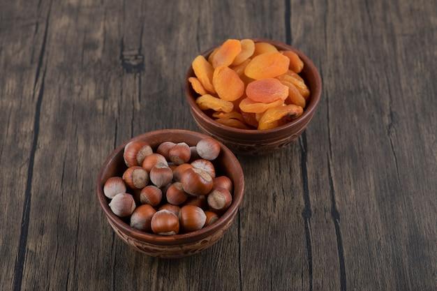 木製のテーブルにドライアプリコットフルーツと健康的なナッツでいっぱいの木製のボウル。