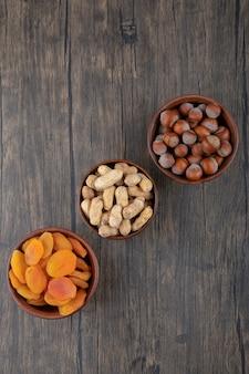 Деревянные миски, полные здоровых орехов с курагой на деревянном столе.