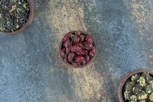 말린 꽃과 로즈힙의 나무 그릇.