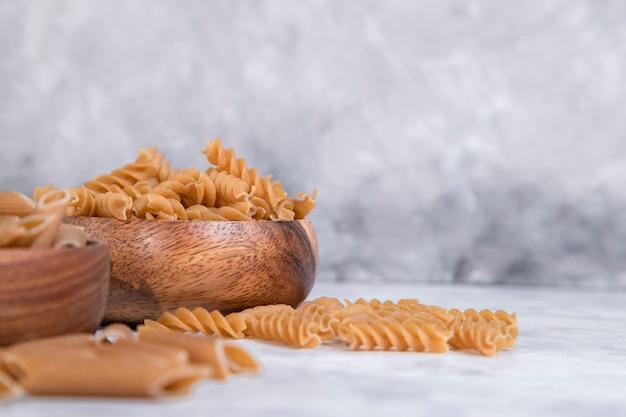 石のテーブルの上に置かれたイタリアの未調理のドライパスタの木製ボウル。高品質の写真