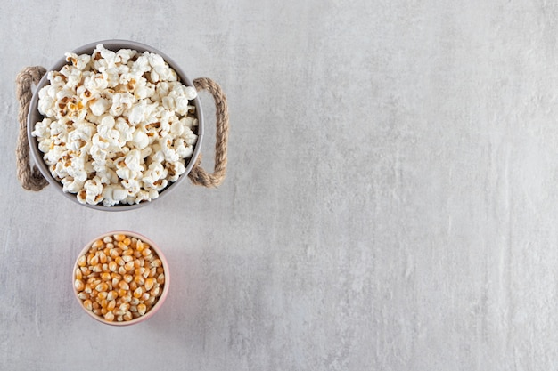 石のテーブルの上のポップコーンと生のトウモロコシの穀粒の木製のボウル。