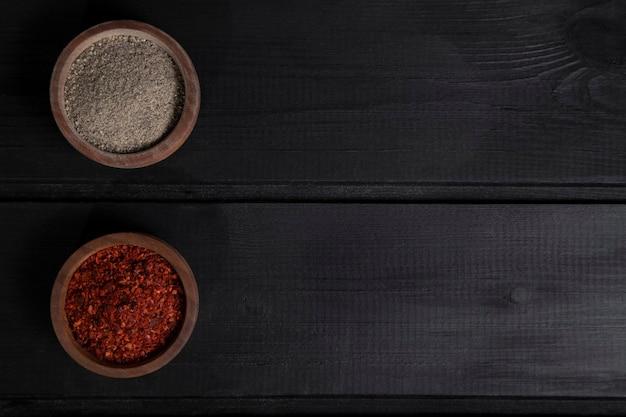 Деревянные миски красного и серого перца приправлены на деревянный стол. фото высокого качества