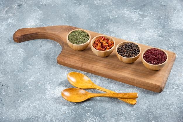 木の板にさまざまなスパイスの木製ボウル。