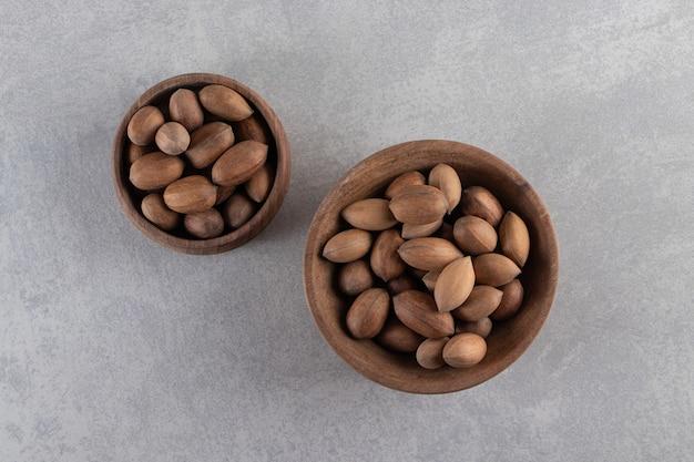 Ciotole di legno di noci sgusciate organiche su fondo di pietra.