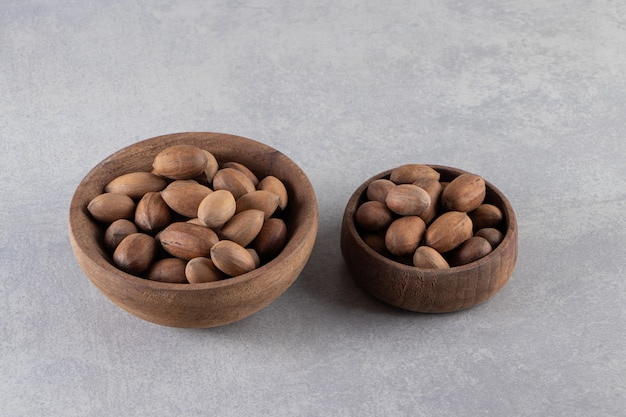 Wooden bowls of organic shelled walnuts on stone surface