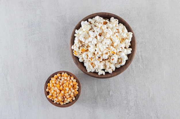 Wooden bowls of popcorn and raw corn kernels on stone background.