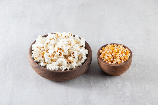 Wooden bowls of popcorn and raw corn kernels on stone surface