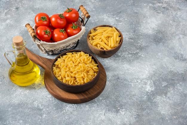 Ciotole di legno di pasta varia cruda e pomodori freschi su marmo.