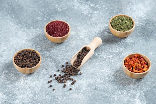 Wooden bowls of various spices on marble background.