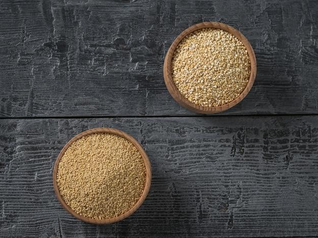 木製のテーブルに斜めにあるアマランスとキノアの種子が入った木製のボウル。グルテンフリーの食品。