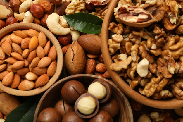 Wooden bowls with different nuts, close up
