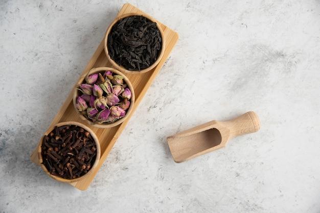 Ciotole in legno con rose essiccate e infuso su tavola di legno.