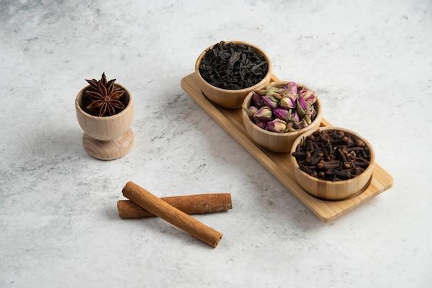 Ciotole in legno con rose essiccate, tè sfusi e chiodi di garofano.